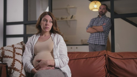 Worried pregnant woman and her husband at home