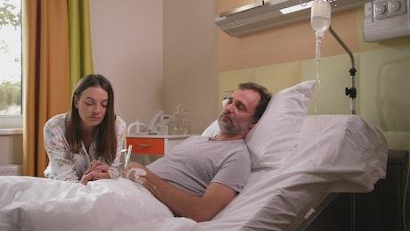 Worried wife at her husbands bedside