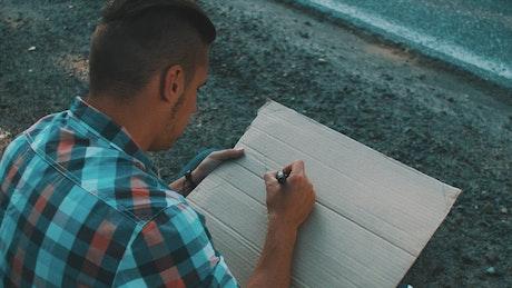 Writing on a cardboard sign