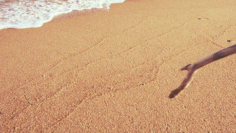"""Writing """"Relax"""" in the sand on a sunny beach"""