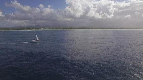 Yacht sailing past an island
