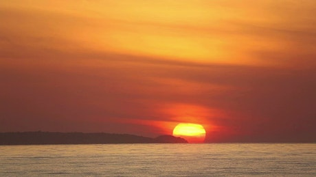 Yellow sun rising at the sea behind the mountains