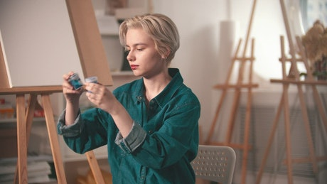 Young artist choosing blue paint at her workshop