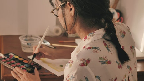 Young artist painting with watercolors
