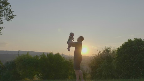 Young baby being raised in the air