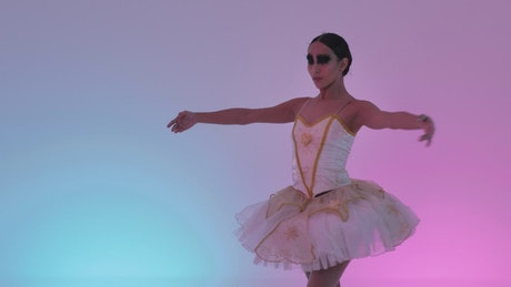 Young ballerina doing movements on a colorful background