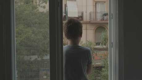 Young boy clapping at a window