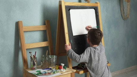 Young boy drawing a house