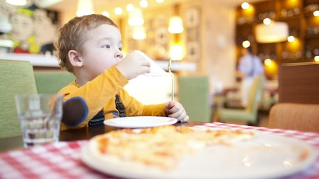 Young boy eating pizza at a cafe