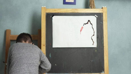 Young boy painting a picture