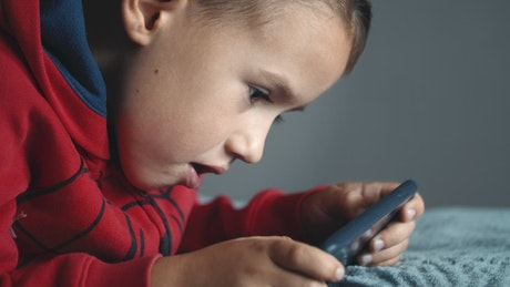 Young boy playing mobile video games on bed