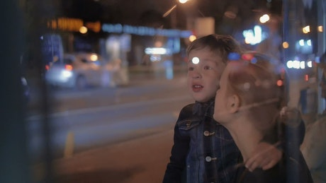 Young boy pointing at city lights