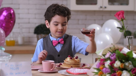 Young boy pouring syrup over pancakes