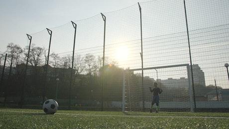Young boy scoring a goal
