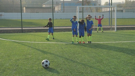 Young boy scoring a goal from a free kick