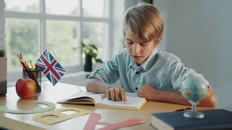 Young boy studies in English classroom