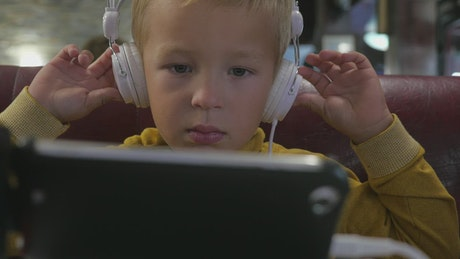 Young boy watching cartoons on a tablete