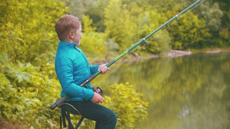 Young boy with a fishing rod at the lake