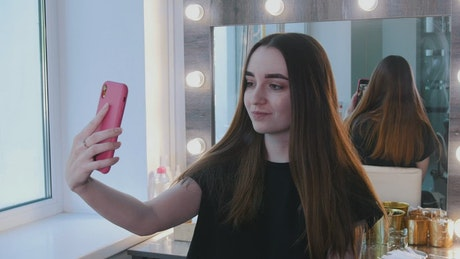 Young brunette woman taking a selfie at the beauty salon