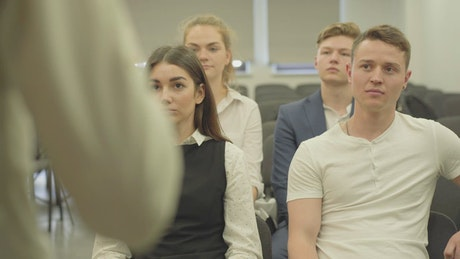 Young business people listen to lecture in conference room