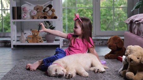 Young child with a puppy taking a selfie