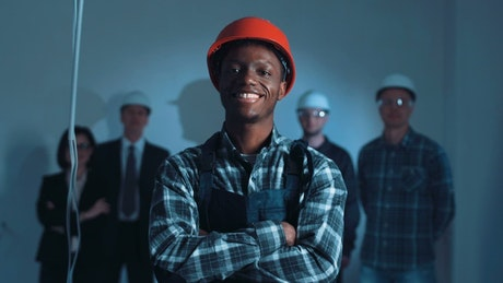 Young construction worker posing with helmet