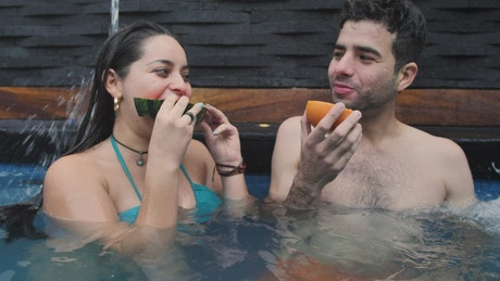 Young couple eating fruit in the swimming pool