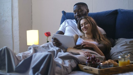 Young couple enjoying a film in bed