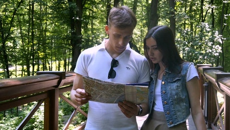 Young couple look at map while walking over park bridge
