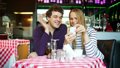 Young couple on a video call in a cafe