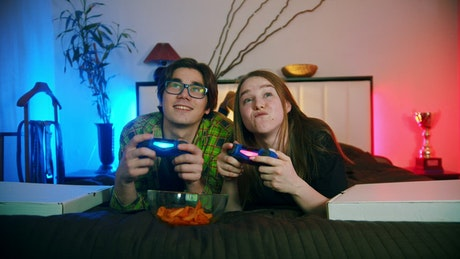 Young couple playing video games on the bed