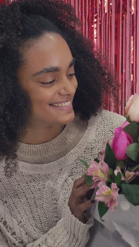 Young delighted woman with bouquet of flowers on Valentine's Day