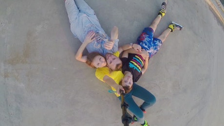 Young family in rollerskates laying on the ground