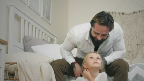 Young father brushing daughters hair