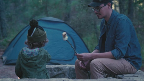 Young father giving roast marshmallow to his daughter outdoors