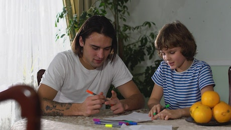 Young father teaches his son to do his homework