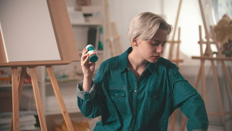 Young female artist selecting tubes of paint