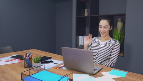 Young female employee having a video call with a client