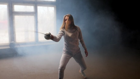 Young female fencer practicing basic movements