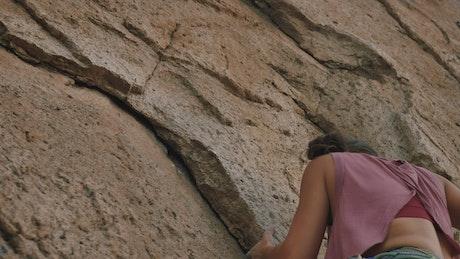 Young female mountaineer climbing a rocky mountain