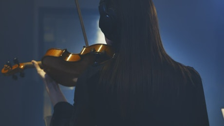 Young female violinist playing in a recording studio