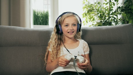 Young girl console gaming on sofa cheers in victory