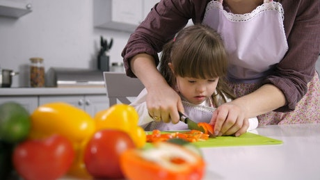 Young girl cutting peppers