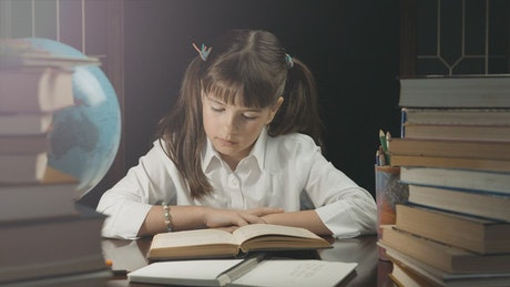 Young girl learns from book in dark room