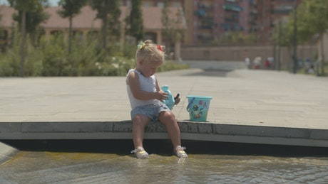 Young girl playing in a city fountain