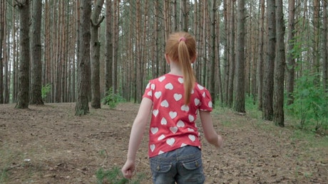 Young girl running through trees