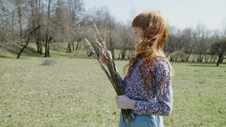 Young girl with a bunch of branches