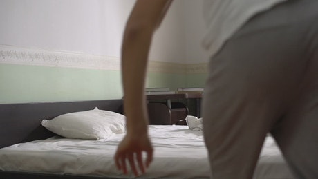Young guy dives into bed and pulls covers up