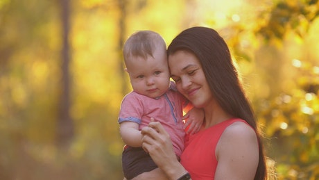 Young happy mother with her baby in nature