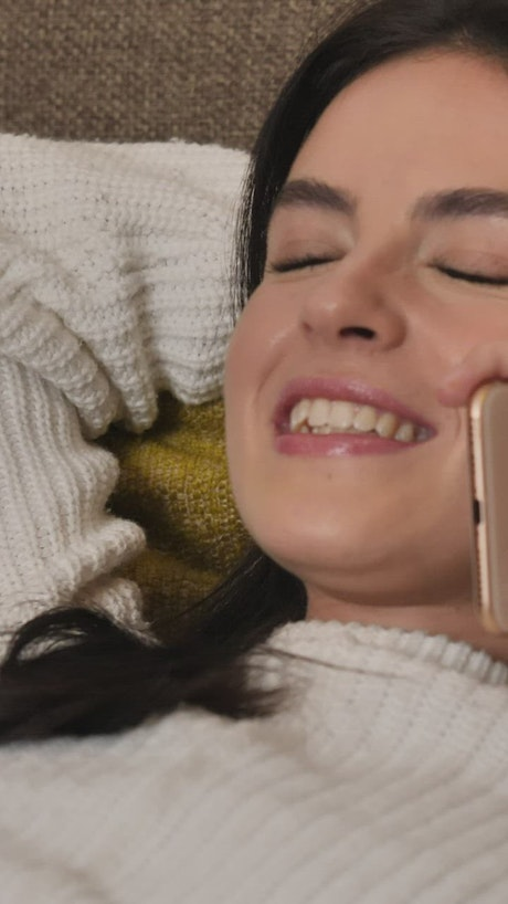Young happy woman laughing during a phone call